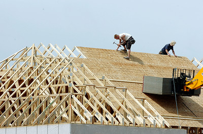Workers assemble the roofing base on one of the buildings at the Winner's Circle in Milton Tuesday afternoon. photo Rick Gargiulo news_winners1_wed 5/26/09