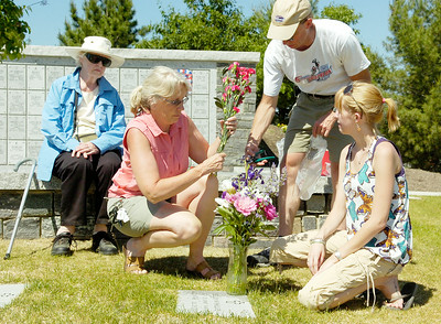From East Schagticoke Margaret Phillips places flowers into a vase with husband Tom, daughter Erica and mother-in-law Mary, of Howes Cave, for father, husband, grandfather after the 11th Annual Memorial Day Ceremony at the Gerald B.H. Solomon Saratoga National Cemetery. Photo Erica Miller 5/31/10 news_SarNtlCem3_Tues