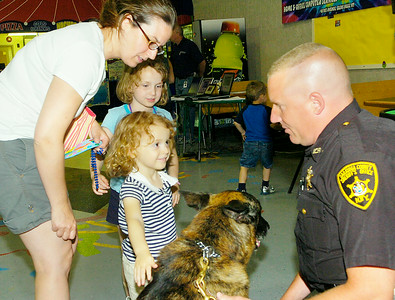 Saratoga County Sheriff's Department deputy Mike Traylor and his K-9 partner Koda greet Allyson Cimino and daughters Hailey, front, and Lisa during Friday's Take 25 children's safety event at the TreePaad Fun Center in Malta.  The Ciminos live in Ballston Lake. Ed Burke 5/28/10