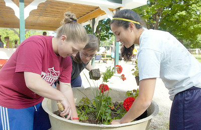 "Saratoga Springs High School students (L-R) Kathleen Allen, 17, Kristin King, 17, and Sarah Campbell, 17, plant flowers into pots surrounding the areas of the backstretch for B.E.S.T. to ""give back"" to the community. Students were also helping at elementary schools and the High Rock Park. Photo Erica Miller 5/29/10 news_GiveBack3_Sat"