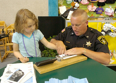 Five year old Lisa Cimino of Ballston Lake is fingerprinted by Saratoga County Sheriff's deputy Mike Traylor during Friday's Take 25 children's safety event at the TreePaad Fun Center in Malta. Ed Burke 5/28/10