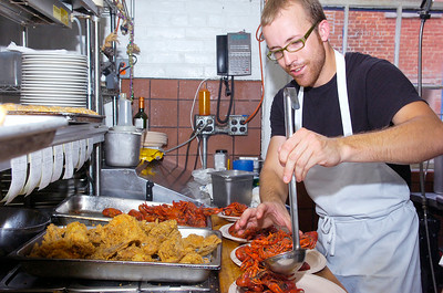 Joey Winterstuiner plates up piles of freshly prepared crawfish for Hattie's Annual Crawfish festival to benefit Caffe Lena Sunday afternoon. Owner Chef Jasper Alexander flew in more than 300 pounds of crawfish for the event. Photo Erica Miller 5/30/10 news_Crawfish1_Mon