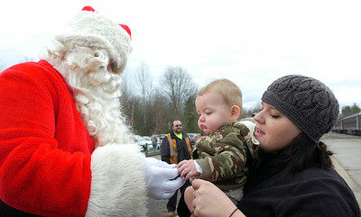 Christina Russell holds up Benjamin Hester, 9 months old of South Carolina, to Santa Clause as he hands out christmas candy canes to children in the audiences  with the Canadian Pacific Holiday Train which stopped at the Saratoga Springs Amtrak Station Monday morning. Photo Erica Miller 11/30/09 news_HolidayTrain3_Tues