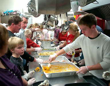At left, eight year old Aidan Kiernan works opposite Saratoga Central Catholic student Dale Long as volunteers crowd the kitchen to help prepare meals during EOC's Community Thanksgiving dinner Thursday at Presbyterian New England Congregational Church. Ed Burke 11/26/09