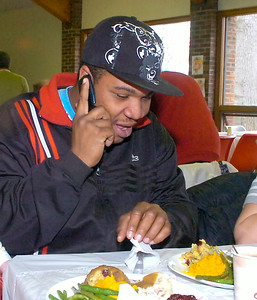 Spending his first Thanksgiving without her, Dakota Tracey of Saratoga Springs talks to his mother while enjoying a Thanksgiving meal at EOC's Community dinner at Presbyterian New England Congregational Church.