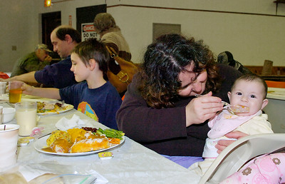 Corine Irish feeds four month old daughter Rebeca during EOC's Community Thanksgiving dinner Thursday at the Presbyterian New England Congregational Church. Corine's husband Mark and son Mark enjoy dinners at left. Ed Burke 11/26/09