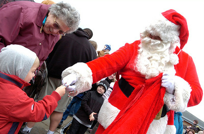 Santa Clause hands over a Candy Cane to Jacob Sankowski, of Clifton Park, with his grandmother Jean Barton, of Burnt Hills, at the Saratoga Springs Amtrak Station Monday morning to see the Canadian Pacific Holiday Train. Photo Erica Miller 11/30/09 cn_HolidayTrain
