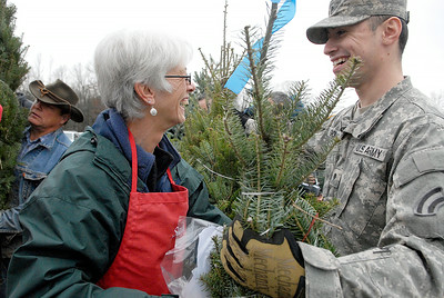 Sally Ellms stuffs handmade ornaments into a tree as Spec. Raymond Gonzolez helped load the FedEx Truck full of trees from local farms at Ellms Farm Monday morning. The troops and other loaded 115 trees for Trees For Troops and Christmas Spirit Foundation. Photo Erica Miller 11/28/11 news_TreesTroops4_Tues