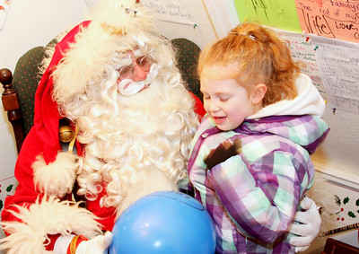 Four year old Nadine Barton Mitchell of Saratoga Springs tells Santa what she wants for Christmas. John R. Dillon photo