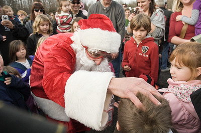 Saratoga Skydiving Santa Claus pats the head of a  child at Ellms Christmas Tree farm Saturday afternoon. Photo Eric Jenks 11/26/11
