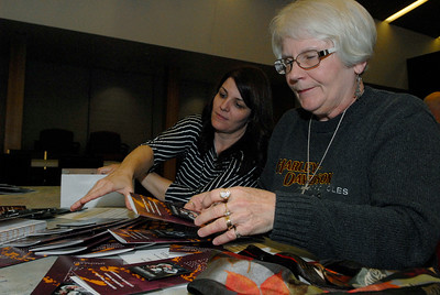Carol Ayers, of Ballston Spa (right), and Heather Conlee, of saratoga Springs, gather together First Night buttons at the as all the pins were attaches to the brochures on Monday evening. There were a total of 7,500 buttons to be attached to brochures by volunteers. Photo Erica Miller 11/28/11 news_ButtonParty1_Tues
