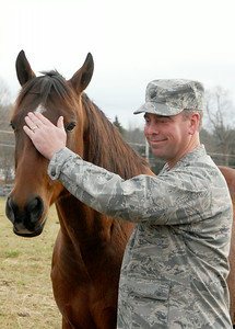 Army Chaplain Todd Luse pets Whiskey, one of the retired horses at the Walpole Farm on Ruggles Road where a new program will introduce veterans to work through their emotional problems by working with horses. Photo Erica Miller 11/29/11 news_WalpoleVet3_Sun