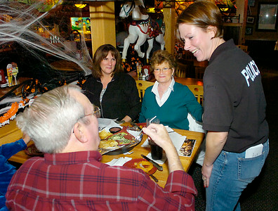 Investigator Laura Emanatian of the Saratoga Springs Police Department waits on Applebee's customers Lindy and Judy Walker along with Kathi Raucci, back left, during Wednesday's Law and Orders event to help raise money for Special Olympics. Ed Burke 10/28/09