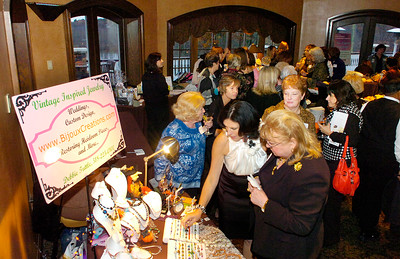 Debbie Tuttle, reaching, of Charlton-based Bijoux Creations shows her jewelry designs to guests at Saratoga Hospital's Just for Women event Thursday at Saratoga National Golf Club. Tuttle uses vintage jewelry to create her modern designs. Ed Burke 10/29/09