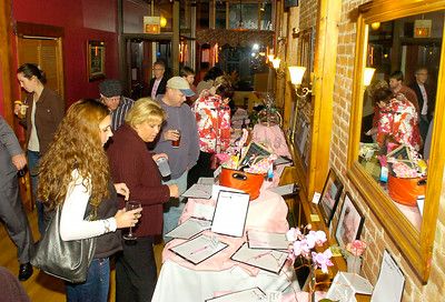 Friends of Jennifer Poitras look at silent auction items during Wednesday's fundraiser at Gaffney's to help Poitras, a longtime Gaffney's employee, who is battling cancer. Ed Burke 10/28/09