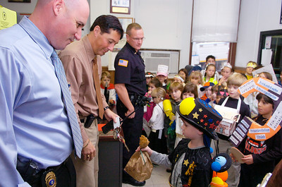 Corwin Freedman, a student from the Saratoga Independent School, hands off a bag of candy to PD officers Glen Vidnanski, Jim Bell and Bob Jillson in thanks for their dedication and hard work. The students also had a chance to sing a song while they were dressed up as different vocabulary words for Halloween. Photo Erica Miller 10/30/09 news_SIScandy2_Sat