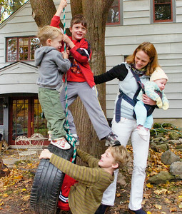 Shannon Hansen holds three month old daughter Erin as sons Peter, bottom, Ian, right, and Emmett pay on a backyard swing at the Ballston Spa home. Ed Burke 10/27/09