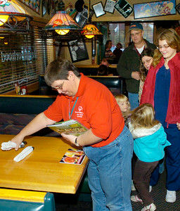 Special Olympian Lee Czajkowski of Saratoga Springs sets a table for customers at Applebee's during Wednesday evening's Law and Orders event. Members of area law enforcement departments helped serve customers to raise money for Special Olympics. Ed Burke 10/28/09