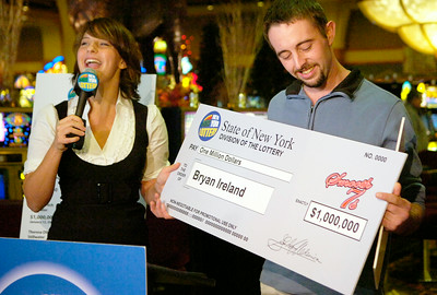 Recent NYS Lottery Winner of One Million Dollars Bryan Ireland, of South Glens Falls, holds up his check with NYS Lottery drawings personality Gretchen Dizer at the Saratoga Gaming and Raceway. Photo Erica Miller 10/29/09 news_Million2_Fr