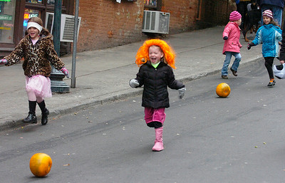 Four year old Madison Warmbier of Saratoga Springs wears an orange wig to match the pumpkin she's rolling down Caroline St. during the Saratoga Springs Fall Festival Saturday. Ed Burke 10/29/11