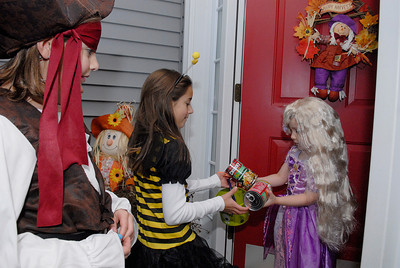 Girls from Girl Scout Troop 3296 of Wilton went Trick-or-Treating in their local neighbor hood in wilton for canned foods. Olivia Harbourne, 3 years old, hands over canned goods to Christine Mallette, 8 years-old (bee), and Adeline McDonough,  8 years-old. Photo Erica Miller 10/31/11 news_TrickTreat1_Tues