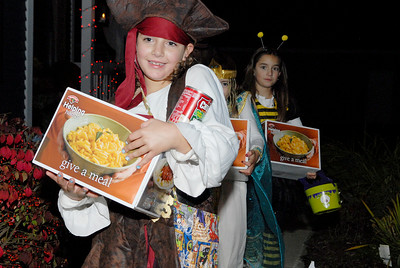 Girls from Girl Scout Troop 3296 of Wilton went Trick-or-Treating in their local neighbor hood in wilton for canned foods. Adeline McDonough, 8 years-old, sister Kaitlin, 6 years-old, and Christine Mallette, 8 years-old, carry boxes of canned goods from one of the houses. Photo Erica Miller 10/31/11 news_TrickTreat3_Tues
