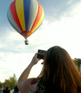 A spectator takes a picture of a balloon during Thursday's launch at Crandall Park in Glens Falls. Ed Burke 9/24/09