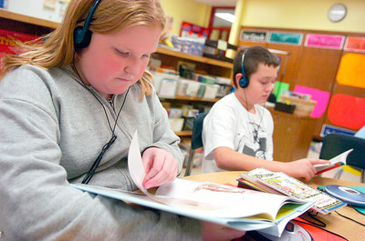 Fifth graders Jamie VanDyke and Dylan Barrera read books while listening to audio in her Literacy Work Station at Ballard Elementary. Photo Erica Miller 10/1/10 wg_LiteracyWork3