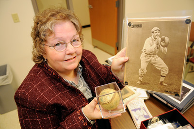 Cathy Eddy holds a photograph of her 1st cousin twice removed Ira Thomas when he played for the Philadelphia A's,  and a baseball from his playing days. The photograph dates back to January 1911 from the Sporting News   photo Rick Gargiulo news_irathomas1_up   11/18/08