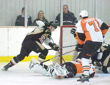 With Phantoms' goalie Jason Bacashihua down on the ice, Penquins' Ryan Schnell digs for the puck during Wednesday's AHL fundraiser for Saratoga Youth Hockey at Saratoga Springs Ice Rink. Ed Burke 9/28/11