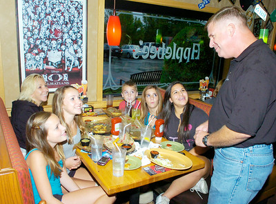 NYS Trooper John Healy talks with a customers Thursday at Applebee's in Wilton during a fundraiser to raise money for Special Olympics. Seated clockwise from front left are Hayly DeLaurie, Amanda Skinkle, Mitzi Szekely, Jonathan Skinkle, Maddy Viger and Chelsea Olmo. The girls are a group of Pop Warner football cheerleaders and Jonathan plays tackle on one of the teams. Ed Burke 9/29/11