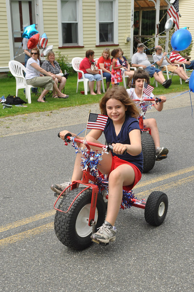 Gillian Jones/North Adams Transcript<br /> Gabriela Nicholson and Martha Leab, both 8 years old, ride their decorated tractor tricycles down Main Street in the Hancock Memorial Day parade Sunday morning.