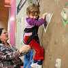 Kezia Chee/North Adams Transcript<br /> <br /> With a little help from her mom, Loretta, Kimberly Mach, 4, scales one of the climbing walls in the Williams College Towne Field House during Williamstown Youth Center's Snowfest fundraiser Sunday afternoon.
