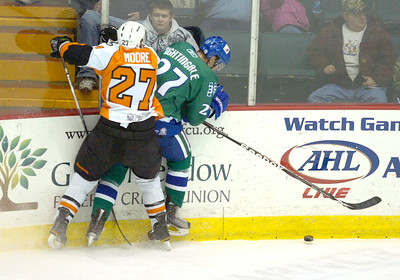Adirondack's Greg Moore checks Connecticut's Jared Nightingale into the boards during Wednesday's AHL game in Glens Falls. Ed Burke 12/15/10