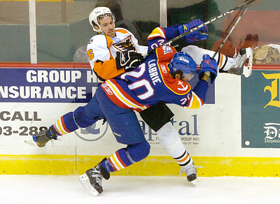 Norfolk's Pierre -Cedric Labrie pastes Adirondack's Andy Roweto the boards during Friday's game in Glens Falls. Ed Burke 11/26/10