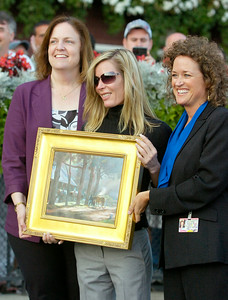 Leading trainer of Saratoga Linda Rice, center, holds a print depicting a scene from Saratoga by Celeste Susany, with Liz Bracken (left), VP of Simulcasting, and Kim Justus, director of guest services, in the winners circle Monday afternoon. Photo Erica Miller 9/7/09 spt_Rice2_Tue