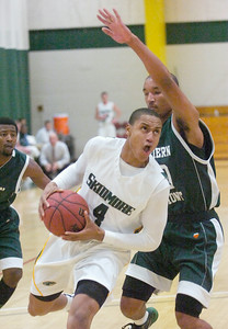 Skidmore's Quenten Howard ducks under defense by Southern Vermont's Robert McQueen during Tuesday's game at Skidmore. Ed Burke 11/22/11