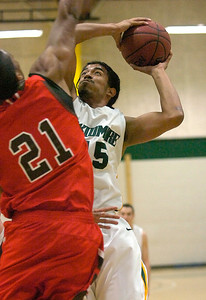 Skidmore's Kyle Clark goes up for a shot against strong defense by St. Lawrence's Ralph Temgoua during Tuesday's basketball matchup at Skidmore. Ed Burke 1/24/12