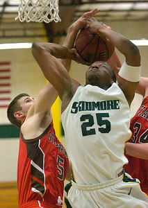 An attemp by Skidmore's Melvis Langyintuo is cut short by tandem defense by St. Lawrence's Brady Condlin, (5) and Janpeter Brase during Tuesday's basketball game at Skidmore. Ed Burke 1/24/12
