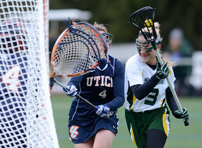 Utica defender Patricia Kane pressure's Skidmore's Emma Harris as she charges to the net and scores on this atempt past Utica's goalie Stephanie Belanger during Wednesday's lacrosse game at Skidmore College. Ed Burke 3/6/13