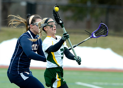 Skidmore's Emma Harris fires a pass as she is pressured by Utica's Keala King during Wednesday's lacrosse game at Skidmore College. Ed Burke 3/6/13