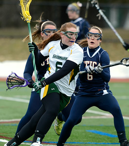 Skidmore's Lexi Melville advances past Utica's Keala King, left, and Megan Kane during Wednesday's lacrosse game at Skidmore College. Ed Burke 3/6/13