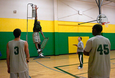Skidmore Men's basketball coach Luke Flockerzi watches as player Melvin Langyintuo performs a vertical jump test during opening night of practice. Players Ivan Paladin (3) and Bobby Langford look on. Ed Burke 10/15/09
