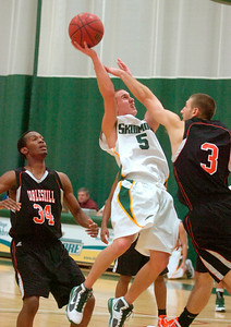 Skidmore's Gerard O'Shea shoots over Cobleskill's Craig Omer during Tuesday's season opener at Skidmore College. Cobleskill's Carl Thomas looks on. Ed Burke 11/17/09