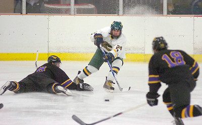 Skidmore's Alex Essaris sprays ice as he darts for the puck between Williams College's Steohen Maier, left, and Eric Rubino during Saturday's game at Saratoga Springs Ice Rink. Ed Burke 2/20/10