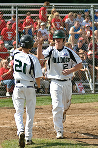 Clifton Park Bulldogs Danny Gregory (Left) and Matt Alverson high five after Alverson crosses home plate during their World Series game against Guilderland Friday Morning. Photo By Eric Jenks 8/27/11