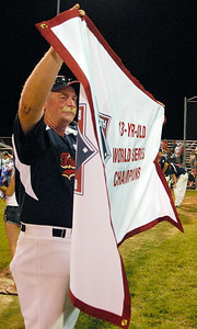 A coach with the Tri Valley holds the winning flag after winning the Babe Ruth League 13-year-old Championship on Friday evening. Photo Erica Miller 8/27/11 spt_BabeRuth1_Sat