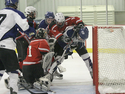 Guilderland/Mohonasen goalie Austin McCrum tries to gain control of the crease as Saratoga's Elliot Hunderford and G/M's James Prunier fight for the puck during the second half of Wednesday's game at Saratoga Springs Ice Rink. Ed Burke 11/28/12