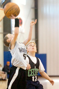 Freddie Smith, Timberwolves, takes a shot at the basket as Charlie Liebers, Celtics, watches during their Division 1 Junior NBA Championship Games at Gavin Park Saturday morning. Photo Erica Miller 2/6/10 spt_JrNBA2_Sun