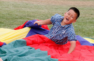 Shaun Walker/The Times-Standard  Ben Her, 7, and others play with a parachute during the Washington After School program in Eureka on Friday afternoon. Participants also played games with balls and other activities.